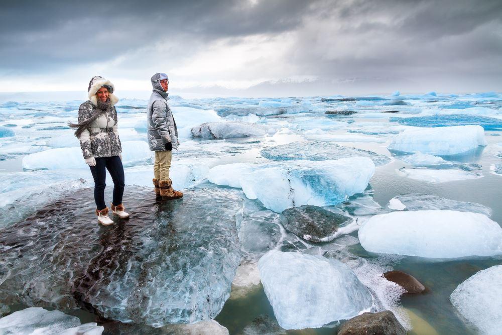 Touristen stehen auf massiven Eisblöcken