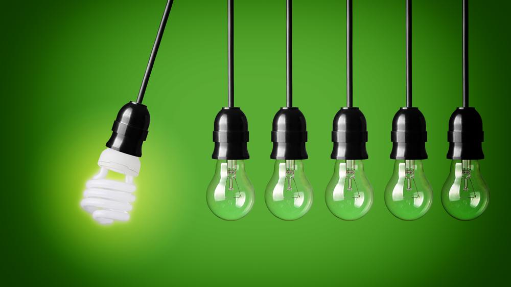 Ein Kugelstoßpendel, auch Newtonpendel genannt, mit einer Energiesparlampe links und fünf herkömmliche Glühbirnen rechts daneben vor einem grünen Hintergrund.