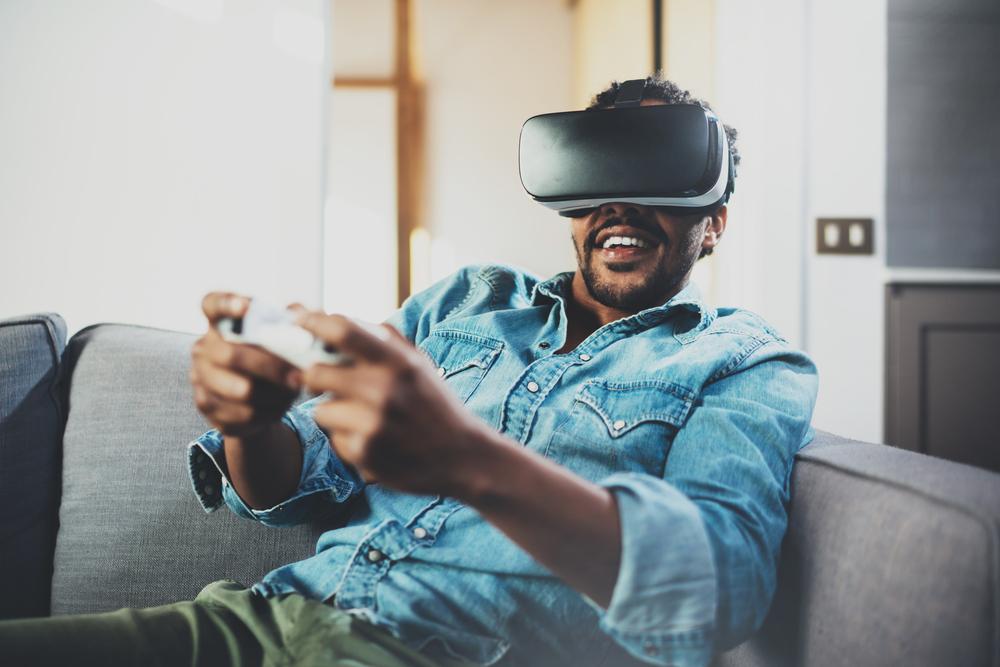 Junger Mann sitzt auf dem Sofa und trägt eine VR Brille