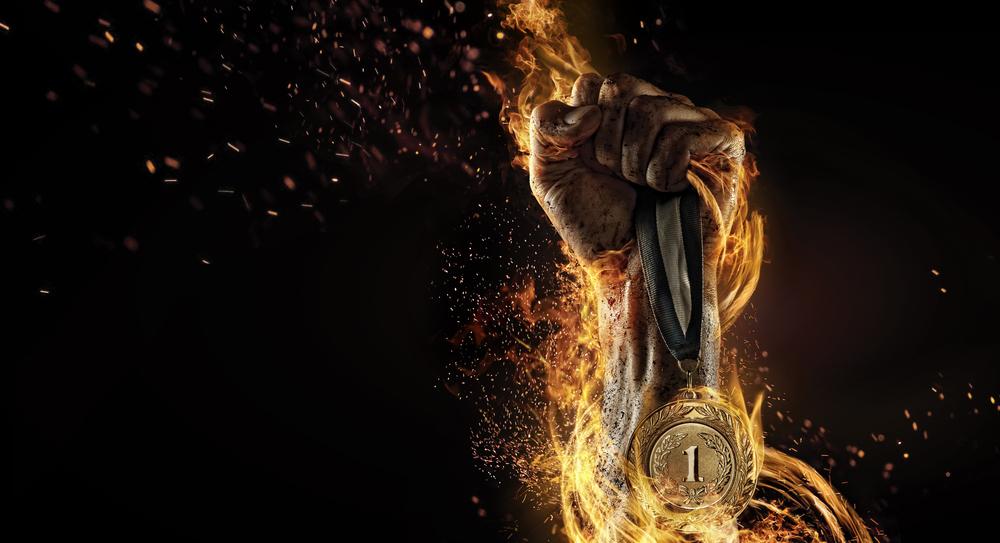 Männliche Hand hält eine Medaille hoch