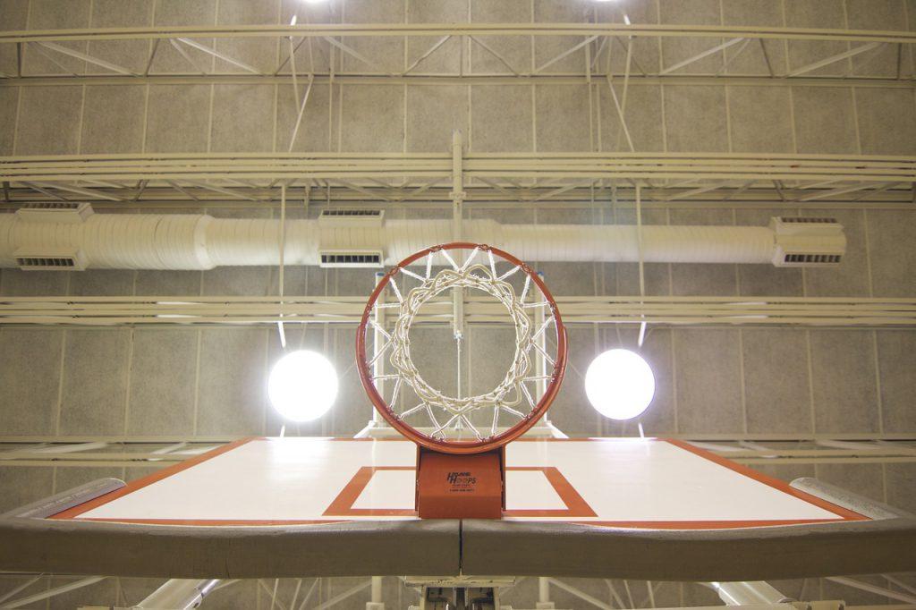 Basketballkorb von unten mit beleuchteter Decke.