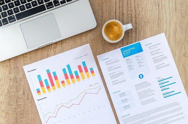 finanzberater laptop kaffee schreibtisch auswertungen analysen